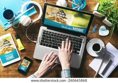Real estate website mock up on laptop screen, tablet and smartphone - stock photo