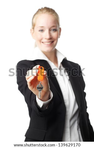 Real estate woman holding out the key to your new home. Isolated on white background, selective focus. Focus on key. - stock photo