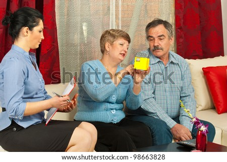 Real estate woman with mature couple in their home showing miniature house - stock photo