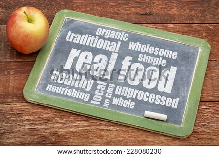 real food word cloud on a blackboard with an apple - healthy lifestyle concept - stock photo