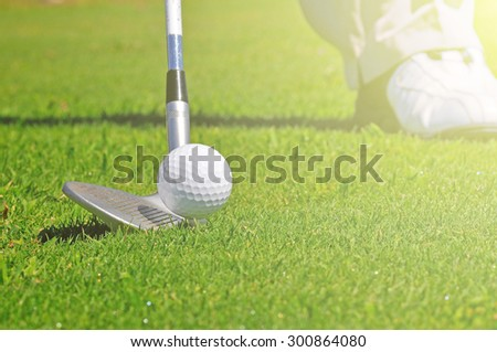 Real golfer ready to strike the ball - stock photo