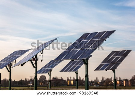 real group of solar panel in the middle of land on sky and building background - stock photo