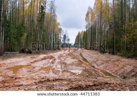 Real latvian road through the autumn forest, it's about 3km near Via Baltica road. Off-road and dirt is everywhere. That's a real situation for countryside roads in our country. - stock photo
