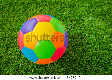 Real leather Colorful multi colour  Soccer ball on green grass - stock photo
