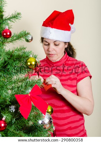 Real life Christmas Holiday scenes: Portrait of the woman in a Santa Claus hat decorates a Christmas tree - stock photo