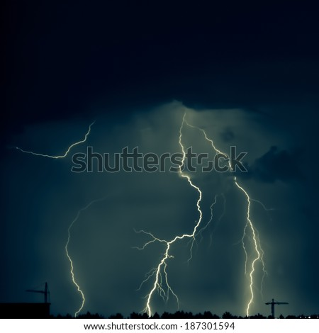 Real lightning. At the bottom are silhouettes of trees and tower cranes. To a photo color tinting is applied - stock photo