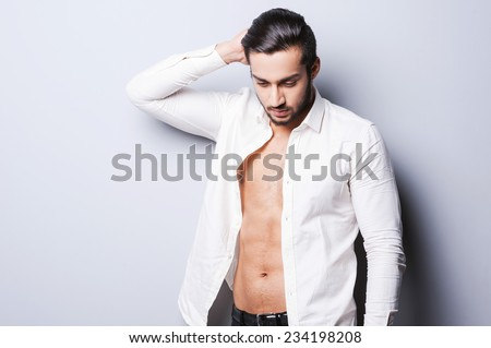 Real macho. Handsome young man in unbuttoned shirt holding hand on head while standing against grey background - stock photo