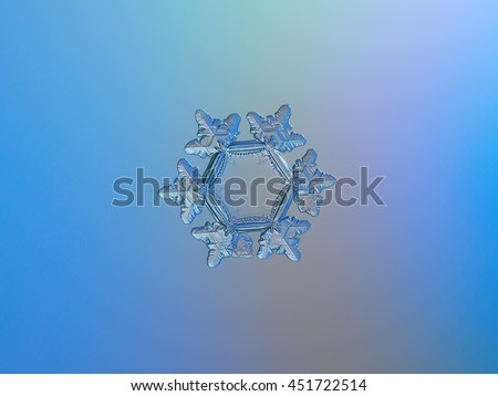 Real macro photo of snowflake, sparkling on light blue gradient background. This is unusual snow crystal: with big, flat and empty central hexagon, relief outer rim and six detailed  arms with ridges. - stock photo