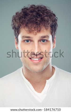 Real Man Portrait - Happy Caucasian man with curly hair and nice smile looking at camera.