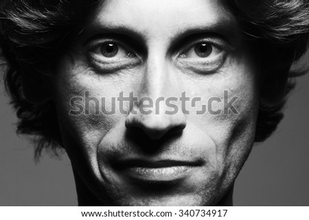 Real natural male beauty concept. Close up portrait of handsome charismatic man posing over gray background in black and white colors. Classic style. Black and white studio shot