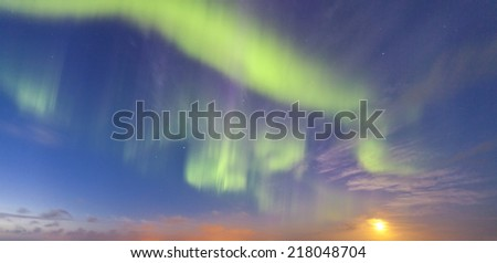 Real Nothern Lights aka Aurora Borealis with moon rising - photographed in Iceland and gently retouched. - stock photo