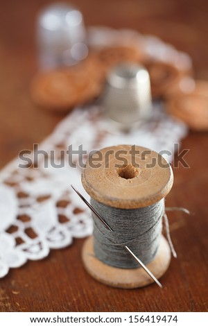 real old reels spools with color treads on old wooded background old thimble and lace backdrop, shallow dof - stock photo
