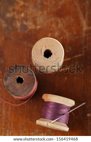 real old reels spools with color treads on old wooded background, shallow dof - stock photo