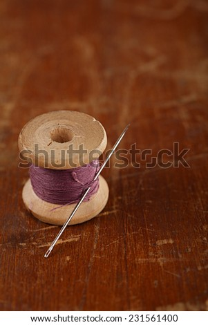 real old reels spoon treads with needle and thimble on old wooden table
