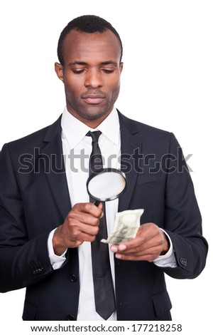 Real or fake? Serious young African man in formalwear looking through a magnifying glass at the paper currency while standing isolated on white background  - stock photo