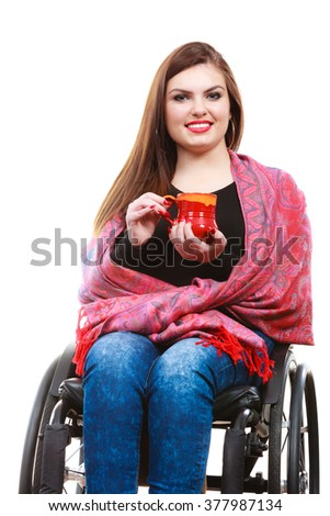 Real people, disability and handicap concept. Teen girl unrecognizable person sitting on wheelchair holding tea mug, studio shot on white - stock photo