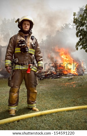 Real People - Firefighter Portrait with house on fire in background - stock photo