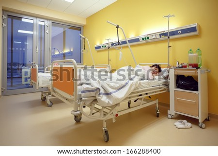 Real people in real situation, sad middle-aged woman lying in hospital with pneumonia - stock photo