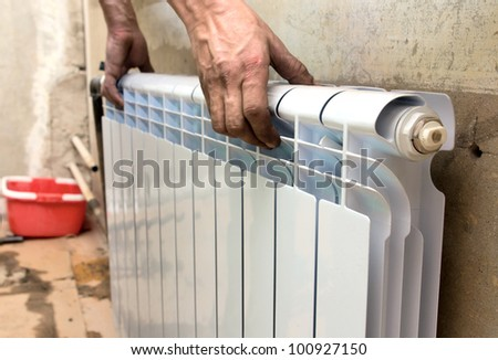 real photo of installation of a radiator - stock photo