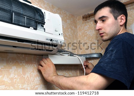 real photo of installation of the conditioner, the worker establishes a decorative casing - stock photo