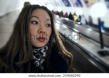 Real portrait of Asian girl on the escalator. - stock photo