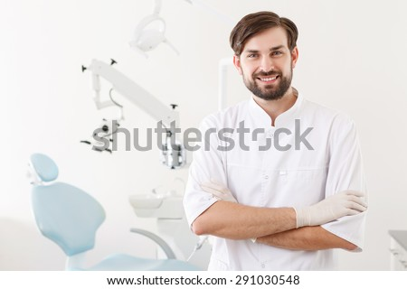 Real professional. Youthful handsome dentist with beard standing on background of stomatology clinic. - stock photo