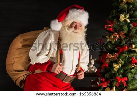 Real Santa Claus carrying big bag full of gifts, at home near Christmas Tree - stock photo