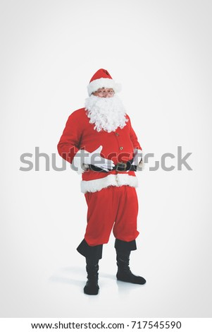 Real Santa Claus carrying big bag full of gifts, isolated on white background.