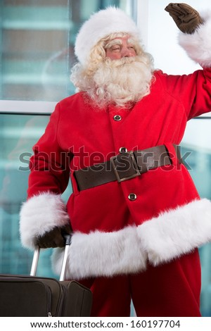 Real Santa Claus standing at airport and waiting for his flight