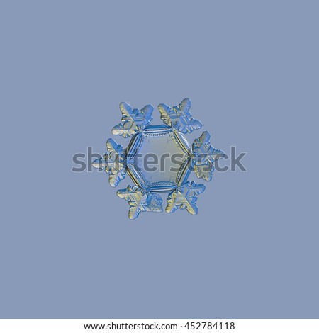 Real snowflake, isolated on pale blue background. This unusual snow crystal have big, flat and empty central hexagon, and relief outer rim and arms. It was captured with blue  / yellow back lighting.