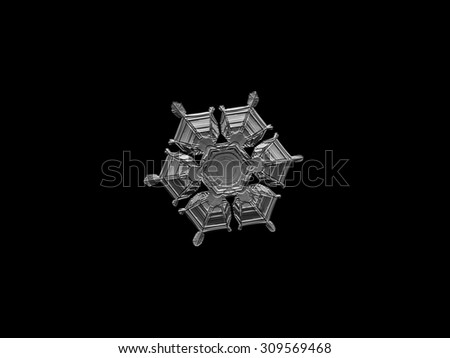 Real snowflake photo on glass with back light. Monochrome version on uniform black background.