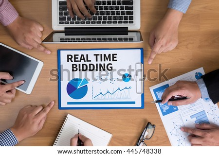 REAL TIME BIDDING Business team hands at work with financial reports and a laptop, top view - stock photo