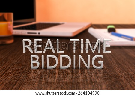 Real Time Bidding - letters on wooden desk with laptop computer and a notebook. 3d render illustration. - stock photo