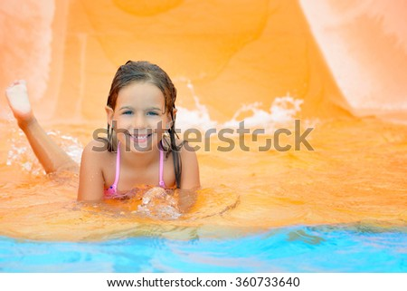 Real toddler girl enjoying her summer vacation water slide at aquapark