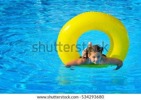 Real toddler girl relaxing at swimming pool, summer vacation concept