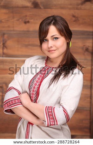 Real Ukrainian woman posing in beautiful traditional costume. Girl standing with her hands clasped on wood background. - stock photo