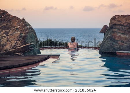 real woman in  pool overlooking the sea  at sunset  in a moment of silence (rear view) - stock photo
