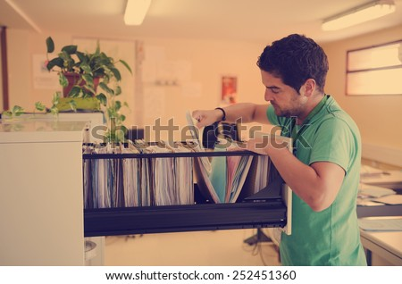 Real worker filing records in office with natural lightning - stock photo