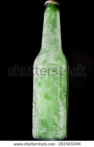 Really cold green bottle of beer on black background - stock photo