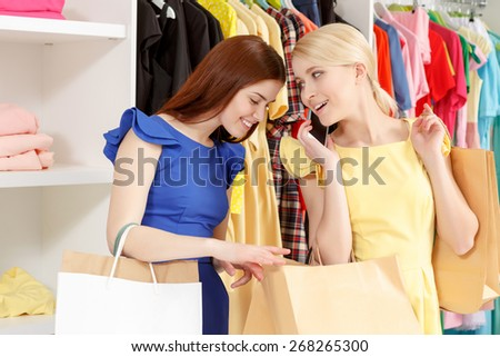 Really cool clothes here. Young smiling shopper speaking over the phone while her friend is peeping inside her paper bags copyspace  - stock photo