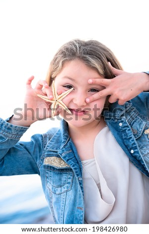 Really funny face, smiling young girl plays with a starfish - stock photo