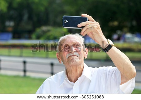 really old man man taking selfie photo with mobile phone in the park - stock photo