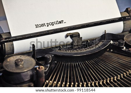 "Really old typewriter. Focus on the text ""Most popular"" written on the sheet of paper. - stock photo"