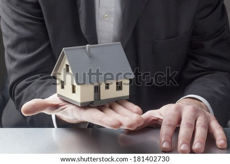 realtor agent's hands with house for sell - stock photo