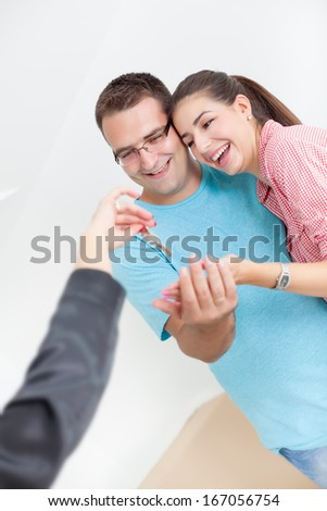 Realtor is giving the keys to an apartment to happy couple  - stock photo
