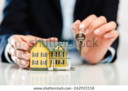 Realtor. Real estate agent with house model and keys  - stock photo