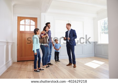 Realtor Showing Hispanic Family Around New Home - stock photo