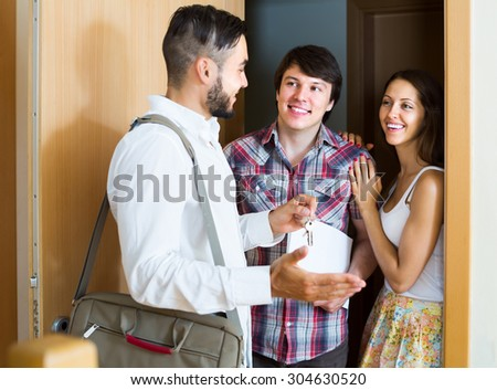 realtor showing new apartment to positive couple - stock photo