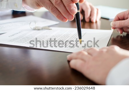 Realtor showing the signature place of a contract with his pen