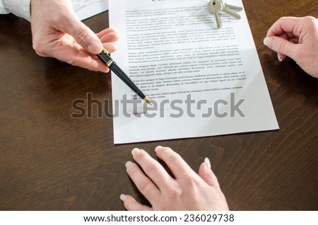 Realtor showing the signature place of a contract with his pen - stock photo